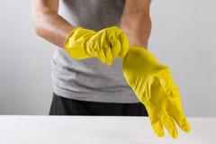 Hombre joven que lleva guantes de goma amarillos Aliste a la limpieza Fotos de archivo