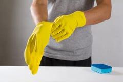 Hombre joven que lleva guantes de goma amarillos Aliste a la limpieza Foto de archivo libre de regalías