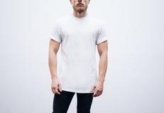 Hombre joven que lleva la camiseta y los tejanos en blanco encendido Fotos de archivo