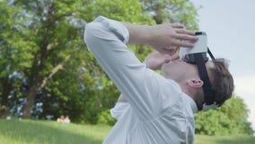Hombre joven que lleva las auriculares de la realidad virtual que caminan en el parque, mirando lados y para arriba, disfrutando  metrajes