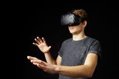 Hombre joven que lleva las auriculares de la realidad virtual en estudio Imagen de archivo libre de regalías