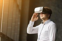 Hombre joven que lleva los vidrios de la realidad virtual en diseño interior moderno Smartphone usando con las auriculares de las Imágenes de archivo libres de regalías