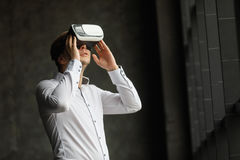 Hombre joven que lleva los vidrios de la realidad virtual en diseño interior moderno Smartphone usando con las auriculares de las Fotografía de archivo