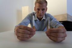 Hombre joven que lucha con el apego que fuma Imagen de archivo