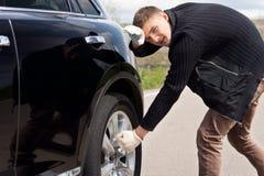 Hombre joven que lucha para cambiar el neumático en su coche Imagenes de archivo