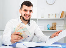 Hombre joven que lucha para pagar facturas de servicios públicos y el alquiler su apartamento Fotos de archivo libres de regalías