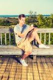 Hombre joven que manda un SMS en el teléfono celular afuera Imagen de archivo libre de regalías