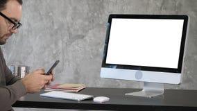 Hombre joven que manda un SMS en el teléfono con un ordenador en el escritorio Visualización blanca fotografía de archivo