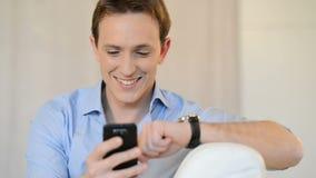 Hombre joven que manda un SMS en el teléfono móvil almacen de metraje de vídeo