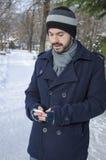 Hombre joven que manda un SMS en invierno frío Fotos de archivo