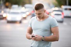 Hombre joven que manda un SMS en la calle Fotografía de archivo libre de regalías