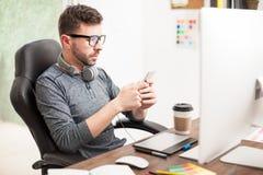 Hombre joven que manda un SMS en la oficina Imagen de archivo libre de regalías