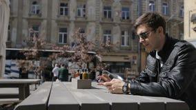 Hombre joven que manda un SMS en smartphone y que usa los relojes elegantes en café Mercancías de compra del hombre caucásico jov almacen de metraje de vídeo