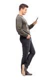 Hombre joven que manda un SMS en su teléfono celular Foto de archivo libre de regalías