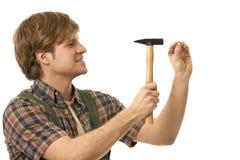 Hombre joven que martilla el clavo Foto de archivo libre de regalías