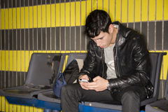 Hombre joven que mecanografía en el metro que espera del smartphone para Fotos de archivo libres de regalías