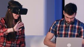 Hombre joven que mecanografía en el ordenador portátil que habla con la muchacha que lleva los vidrios de la realidad virtual Imagen de archivo