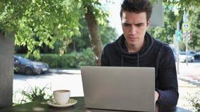 Hombre joven que mecanografía en el ordenador portátil mientras que se sienta en terraza del café metrajes