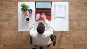 Hombre joven que mecanografía en el ordenador portátil y que mira en la exhibición, topshot, sentándose detrás de la tabla con lo almacen de video