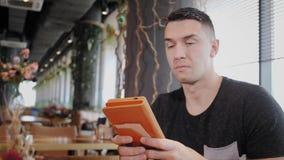 Hombre joven que mecanografía en la tableta, charla, bloging Trabajo del Freelancer sobre netbook en coworking moderno Programado almacen de metraje de vídeo