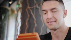 Hombre joven que mecanografía en la tableta, charla, bloging Trabajo del Freelancer sobre netbook en coworking moderno Programado metrajes