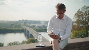 Hombre joven que mecanografía en su tableta en la concentración profunda mientras que coloca en un puente con el ajuste del sol d almacen de metraje de vídeo