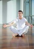 Hombre joven que medita en el gimnasio imagen de archivo