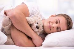 Hombre joven que miente debajo de una manta con el oso de peluche Foto de archivo