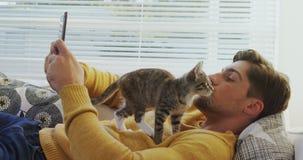 Hombre joven que miente en el sofá usando el teléfono móvil mientras que gato que camina en él 4K 4k almacen de video