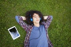Hombre joven que miente en hierba y música que escucha Fotos de archivo