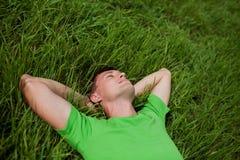 Hombre joven que miente en la hierba Foto de archivo