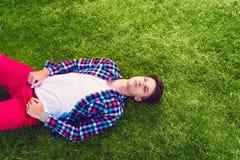 Hombre joven que miente en la hierba Imagenes de archivo