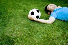 Hombre joven que miente en la hierba Fotografía de archivo