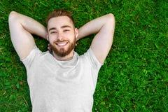 Hombre joven que miente en la hierba en parque Imagenes de archivo