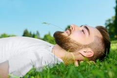 Hombre joven que miente en la hierba en parque Fotos de archivo libres de regalías