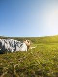 Hombre joven que miente en la hierba verde Imagenes de archivo
