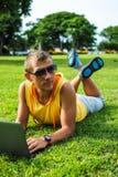 Hombre joven que miente en la hierba y que trabaja con el ordenador portátil Fotografía de archivo libre de regalías