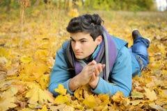 Hombre joven que miente en parque Imagen de archivo libre de regalías