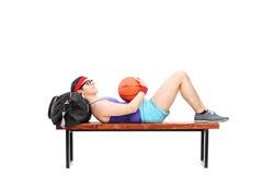 Hombre joven que miente en un banco y que lleva a cabo baloncesto Imagenes de archivo