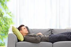 Hombre joven que miente en un sofá en casa Fotografía de archivo