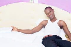 Hombre joven que miente en una cama con un libro a disposición Imagen de archivo