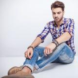 Hombre joven que mira abajo mientras que se sienta en el piso Fotografía de archivo libre de regalías
