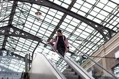 Hombre joven que mira abajo mientras que se coloca en la escalera móvil Imágenes de archivo libres de regalías