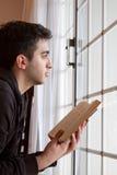 Hombre que sostiene la biblia que mira hacia fuera la ventana Imagenes de archivo
