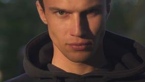 Hombre joven que mira agresivamente la cámara, odio, deseo de la venganza, primer de la cara almacen de video