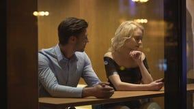 Hombre joven que mira al blonde hermoso atractivo con interés, ligón en la barra metrajes
