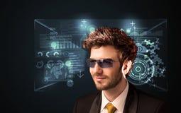 Hombre joven que mira con los vidrios de alta tecnología elegantes futuristas Fotos de archivo libres de regalías
