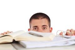 Hombre joven que mira detrás de sus documentos del estudio imagenes de archivo