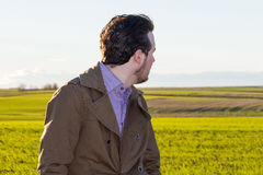 Hombre joven que mira detrás en el campo foto de archivo