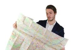 Hombre joven que mira el mapa de la ciudad, confuso o perdido Foto de archivo libre de regalías